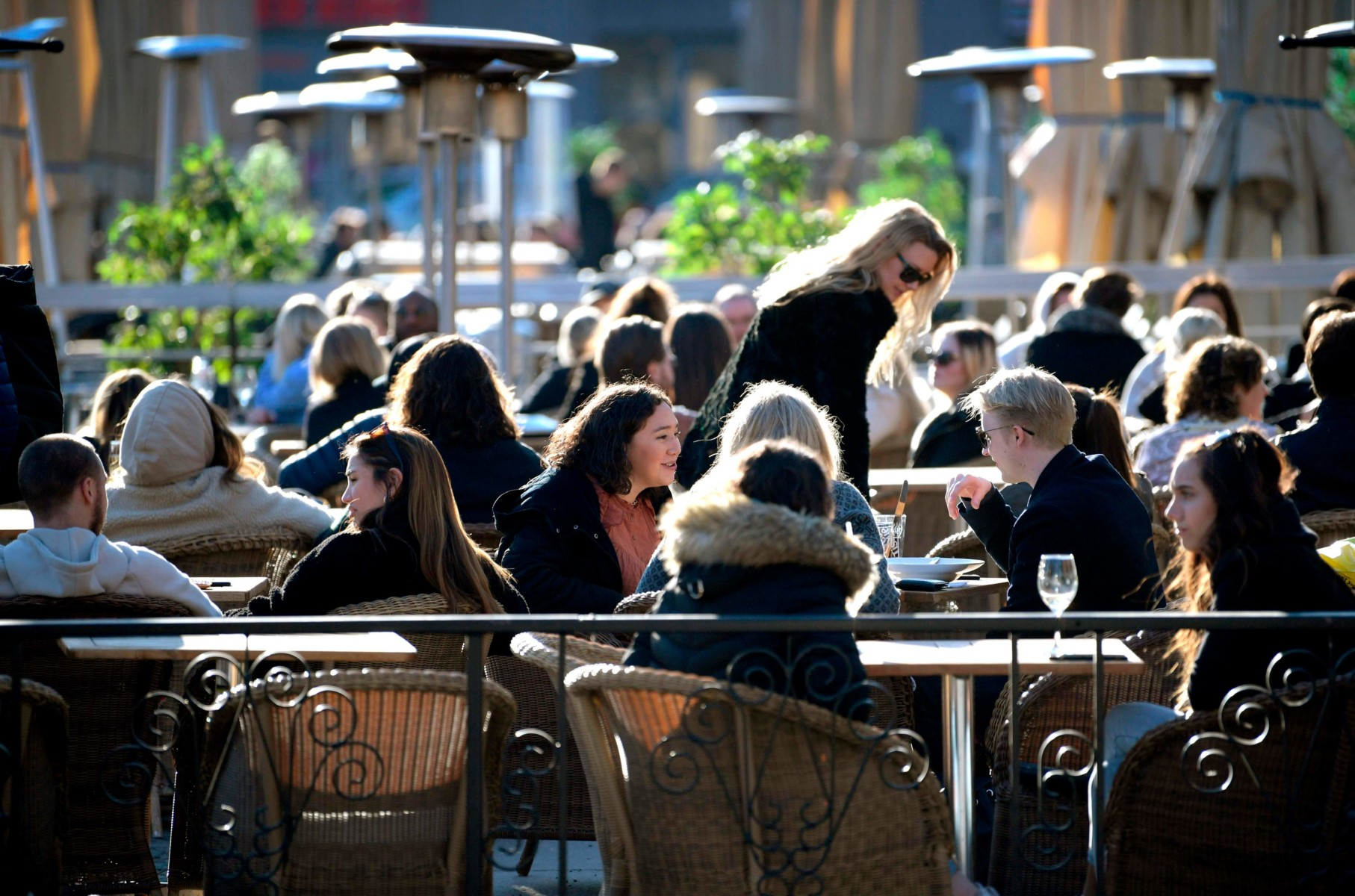 Dozens of Swedes enjoy the sun at a terrace on a square in central Stockholm