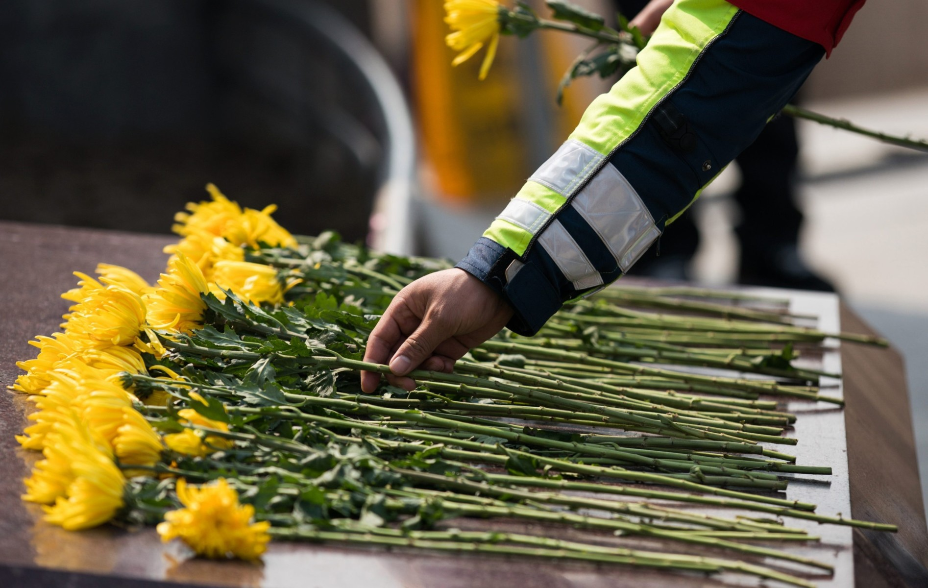Chinese policemen lay flowers during a memorial to mourn for victims of COVID-19 in Shanghai